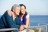 Uomo anziano con la figlia adulta, guardando oltre la ringhiera in mare — Foto Stock