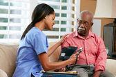 Enfermera a visitante paciente masculino senior en casa — Foto de Stock