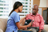 Nurse Visiting Senior Male Patient At Home — Foto Stock