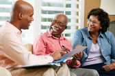 Financieel adviseur praten met senior koppel thuis — Stockfoto