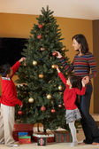 Mother And Children Decorating Christmas Tree — Стоковое фото
