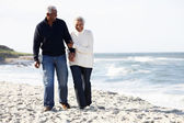 Senior Couple Walking Along Beach Together — Stock Photo