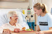 Teenage Volunteer Serving Senior Female Patient Meal In Hospital — Stock Photo