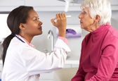 Doctor Examining Senior Female Patient's Eyes — Stockfoto