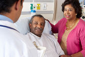 Arts praten met senior koppel op ward — Stockfoto