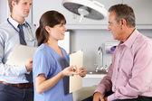 Manlig patient behandlas av läkare och praktikant — Stockfoto