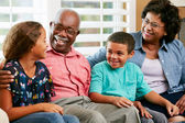 Grandparents With Grandchildren Sitting On Sofa And Talking — Foto Stock