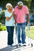 Mulher sênior, ajudando o marido com moldura para caminhadas — Foto Stock