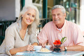 Senior Woman Enjoying Snack At Outdoor Cafe — Stock Photo
