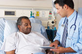 Doctor Using Digital Tablet In Consultation With Senior Patient — Stock Photo