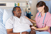 说话高级男性病人在病房的护士 — 图库照片