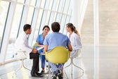 Medical Team Meeting Around Table In Modern Hospital — Stok fotoğraf