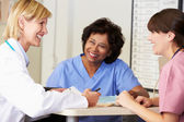Doctor And Nurses In Discussion At Nurses Station — Stock Photo