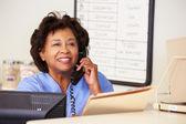 Nurse Making Phone Call At Nurses Station — Stock Photo