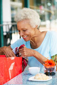 Senior Woman Enjoying Snack At Outdoor Cafe After Shopping — Stock Photo