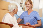 Nurse Taking To Senior Female Patient Seated In Chair By Hospita — Stock Photo