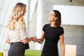 Duas empresárias apertando as mãos no escritório moderno — Foto Stock