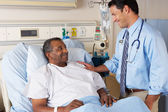 Doctor Visiting Senior Male Patient On Ward — Stockfoto