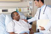 Läkare besöker äldre manlig patient på ward — Stockfoto