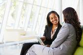 Mujeres empresarias con tableta digital sentado en la oficina moderna — Foto de Stock