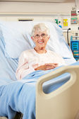 Portrait Of Senior Female Patient Relaxing In Hospital Bed — Stock Photo