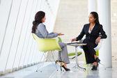Due imprenditrici incontro intorno a tavolo in ufficio moderno — Foto Stock
