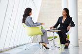 Two Businesswomen Meeting Around Table In Modern Office — Stock Photo