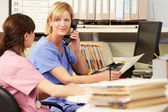 Two Nurses Working At Nurses Station — Stock Photo