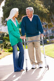 Senior Woman Helping Husband With Walking Frame — Stock Photo