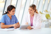 Doctora y enfermera teniendo reunión en cantina hospital — Foto de Stock