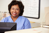 Nurse Using Computer At Nurses Station — Stock Photo