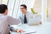 Dos empresarios a tener reunión alrededor de mesa en la oficina moderna — Foto de Stock