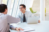 Two Businessmen Having Meeting Around Table In Modern Office — Foto de Stock