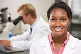男性和女性科学家在实验室中使用显微镜 — 图库照片