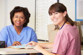 Two Nurses In Discussion At Nurses Station — Stock Photo