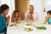 Familie zeggen genade voor de maaltijd thuis — Stockfoto