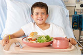 Boy Eating Meal In Hospital Bed — Stock Photo