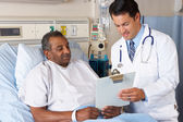 Lekarz tłumacząc formularz zgody pacjenta seniorów — Zdjęcie stockowe