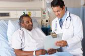 Médecin expliquant le formulaire de consentement au patient senior — Photo