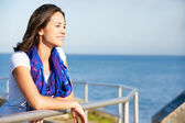 Hispanic Woman Looking Over Railing At Sea — Stock Photo