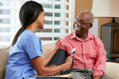 Infirmière visiteuse senior homme patient à la maison — Photo