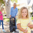 Royalty-Free Stock Photo: Mother And Daughters Picking Up Litter In Suburban Street