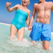Senior Couple Having Fun In Sea On Beach Holiday — Stock Photo