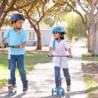 Boy And Girl Wearing Safety Helmets And Riding Scooters - Stock Photo