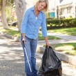 Royalty-Free Stock Photo: Woman Picking Up Litter In Suburban Street