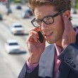 Businessman Speaking On Mobile Phone By Noisy Freeway - ストック写真