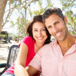 Romantic Couple Sitting On Park Bench Together - Stockfoto