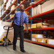 Man Pulling Pallet In Warehouse - Foto Stock