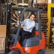 Stock Photo: Man Driving Fork Lift Truck In Warehouse