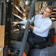 Man Driving Fork Lift Truck In Warehouse — Stock Photo #25045863